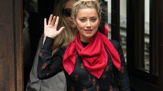"""Actress Amber Heard gestures as she arrives at the High Court for a hearing in Johnny Depp's libel case, in London, Wednesday July 15, 2020. Depp is suing News Group Newspapers, publisher of The Sun, and the paper's executive editor, Dan Wootton, over an April 2018 article that called him a """"wife-beater."""" The Sun's defense relies on a total of 14 allegations by Heard of Depp's violence. He strongly denies all of them."""