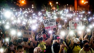 Hundreds of Black Lives Matter protesters hold their phones aloft