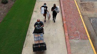 In this July 31, 2020, file photo, a family carries their belongings while college students begin moving in for the fall semester at N.C. State University in Raleigh, N.C.