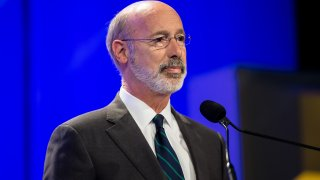 Gov. Tom Wolf stands at a lectern and in front of a microphone.