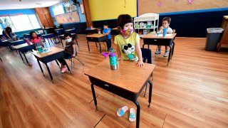 In this July 9, 2020, file photo, children in a pre-school class wear masks and sit at desks spaced apart as per coronavirus guidelines during summer school sessions in Monterey Park, California.
