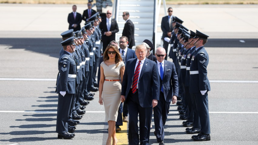 U.S. President Donald Trump, center, U.S. First Lady Melania Trump, left, and Woody Johnson, U.S. ambassador to the United Kingdom, make their way to Marine One after arriving nat London Stansted Airport in Stansted, U.K., on Thursday, July 12, 2018. Trump will avoid London as much as possible as he's whisked off on a tour of prime British real estate to keep him away from protesters during his U.K. visit.