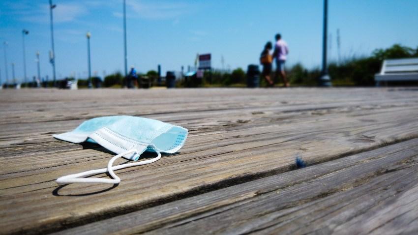 A mask lies on the boardwalk