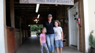 """Timea Hunter poses for a photograph with her children Lena, left, and Liam, right, at the Family Horse Academy, where she is hoping to organize education for a group of children during the coronavirus pandemic, Friday, July 31, 2020, in Southwest Ranches, Fla. Confronting the likelihood of more distance learning, families across the country are turning to private tutors and """"learning pods"""" to ensure their children receive some in-person instruction. The arrangements raise thorny questions about student safety, quality assurance, and inequality."""
