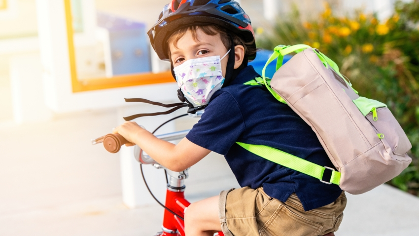 Little boy riding a bicycle wearing a protective mask.