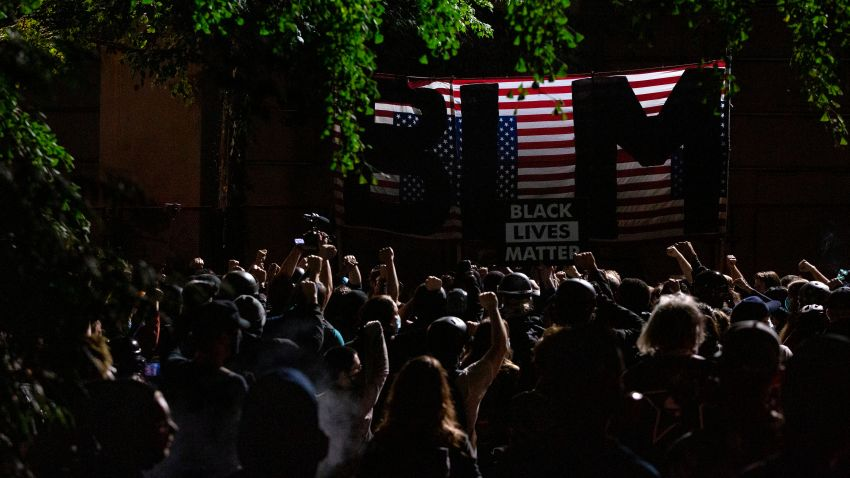 "Protesters raise their fists in solidarity as they listen to a speaker during a night of protest against racial injustice on July 31, 2020 in Portland, Oregon, as the letters BLM for 'Black Lives Matter' are seen on a flag of the United States that hangs upside down. - US federal officers will stay in the protest-wracked city of Portland until local law enforcement officials finish a ""cleanup of anarchists and agitators,"" the US President said."