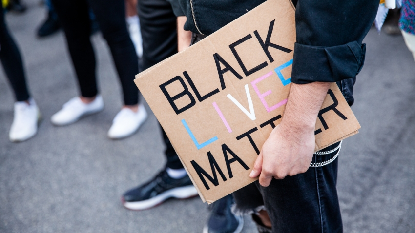 A protester holds a sign in support of Black Lives Matter