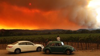 Local residents sit next to a vineyard as they watch the LNU Lightning Complex fire burning in nearby hills on August 20, 2020 in Healdsburg, California.