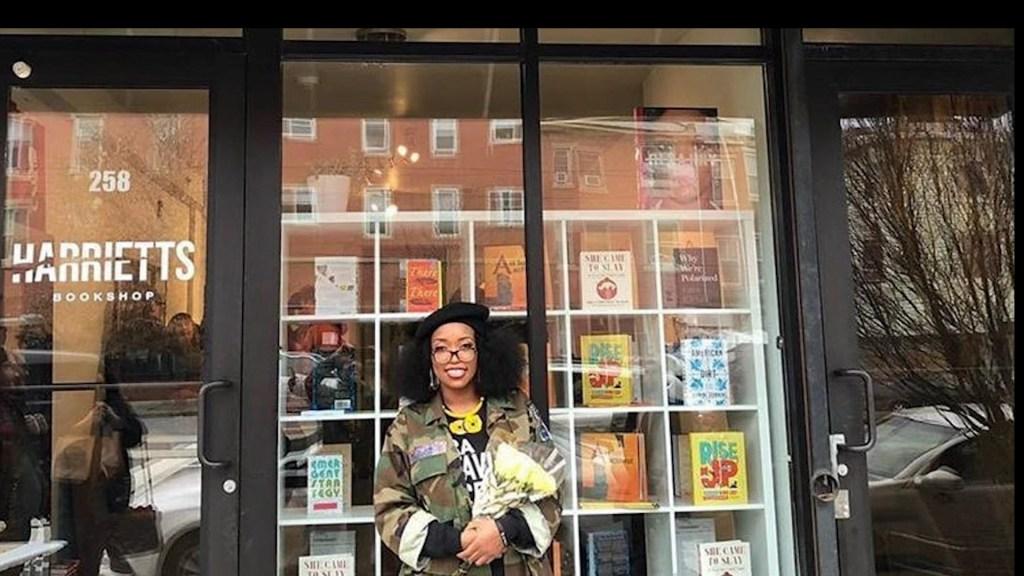 Woman standing in front of her bookshop in Philadelphia