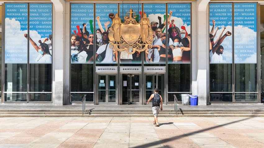 A man walks toward Philadelphia's Municipal Services Building, where a mural depicts people raising their fists in the air as a tribute to the Black Lives Matter movement.