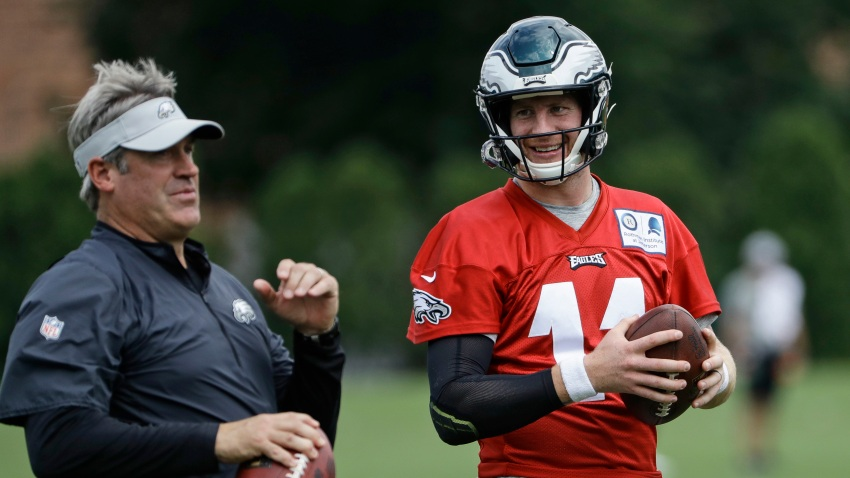 In this Aug. 21, 2018, file photo, Philadelphia Eagles quarterback Carson Wentz and coach Doug Pederson talk during practice at the team's NFL football training facility in Philadelphia