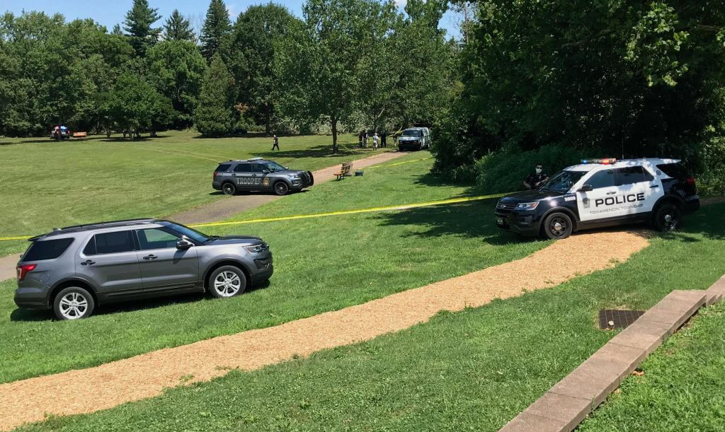 Police SUVs park at Fischer's Park in Montgomery County, Pennsylvania, as crime scene tape surrounds a grassy area.