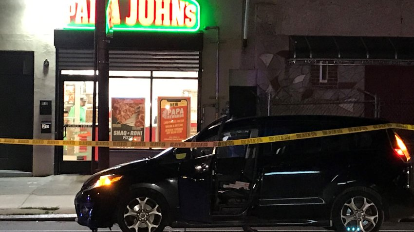 A van is parked in front of a Papa John's pizzeria and behind crime scene tape at the site of a deadly drive-by shooting.