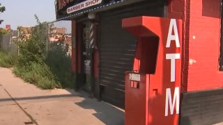 A red ATM that was blown up stands next to a West Philadelphia barber shop.