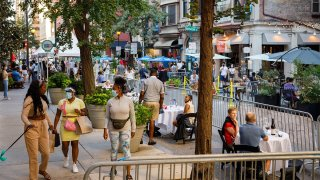 Diners and walkers socially distanced on a street