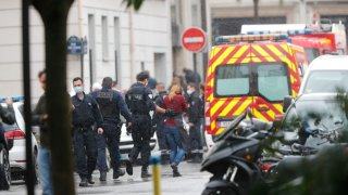 French police officers patrol the area after a knife attack near the former offices of satirical newspaper Charlie Hebdo