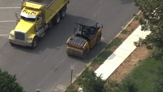 A road roller sits next to a dump truck near a Delaware County, Pennsylvania, middle school.