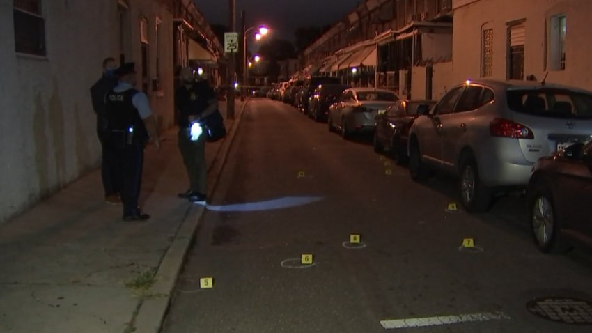 Philadelphia Police Department investigators stand on a sidewalk as bullet casings and evidence markers lay on the ground after a shooting.