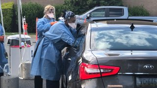 People in PPE administer drive-up COVID tests