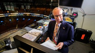 In this May 27, 2019, file photo, hours before Game 1 of the Stanley Cup Finals between the Boston Bruins and the St. Louis Blues at TD Garden in Boston, NBC hockey play-by-play announcer Mike Emrick does voice overs in the empty arena.