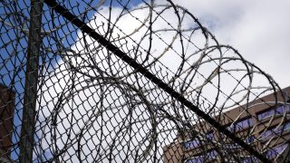 In this April 9, 2020, file photo, a fence surrounds the Cook County jail complex in Chicago, Illinois.