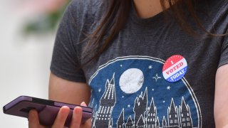 """A woman wears an """"I VOTE STICKER"""" after casting her early voting ballot at the City Hall satellite polling station on October 27, 2020 in Philadelphia, Pennsylvania."""