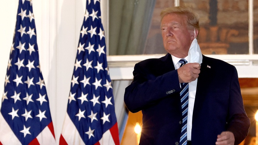 U.S. President Donald Trump removes his mask upon return to the White House from Walter Reed National Military Medical Center on October 05, 2020 in Washington, DC. Trump spent three days hospitalized for coronavirus.