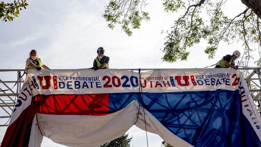 Workers hang banners outside of Kingsbury Hall on the University of Utah campus ahead of the U.S. vice presidential debate in Salt Lake City, Utah, Oct. 5, 2020.