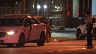 A Philadelphia Police Department officer stands across a police cruiser at the site of a hit-and-run crash.