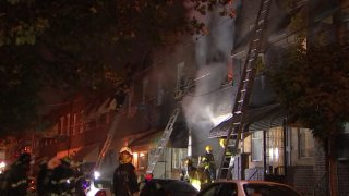 Smoke billows from a South Philadelphia row home as firefighters douse water on the fire.