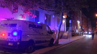 A Philadelphia Police Department van is parked on the sidewalk in front of a row home on a block where two Temple University students fell off a roof.