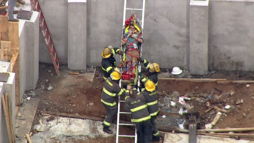 A man lays on a stretcher as firefighters surround him and help pull him up a ladder after the man was hurt from a fall into an open basement.