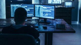 Man sits looking at computer screens