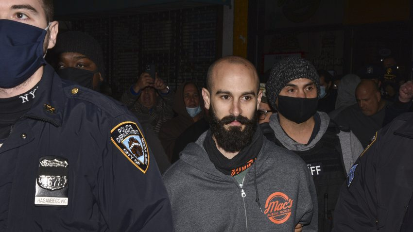 Mac's Public House co-owner Danny Presti is taken away in handcuffs after being arrested by New York City sheriff's deputies