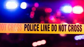 Police sirens flash behind police crime scene tape