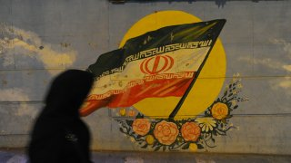 TEHRAN, IRAN - SEPTEMBER 18: An Iranian woman walks past an Iranian flag painted on a wall, as Iranians try to lead normal lives while bracing for renewed US sanctions on September 18, 2018 in Tehran, Iran. After President Donald Trump withdrew the US from the 2015 Iran nuclear deal last spring, Washington reimposed one set of sanctions in August, and will impose more on November 4, which are designed to cut-off Iran's oil revenue. So far this year the Iranian currency, the rial, has tumbled in value, prices have soared, and shortages of some goods like diapers/nappies have appeared.