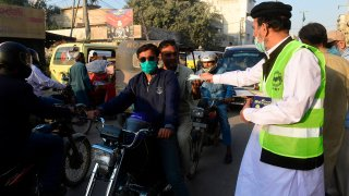 A Arsalan Helpline Welfare Trust (AHWT) worker distributes face masks to motorists along a street as a preventive measure against the spread of the Covid-19 coronavirus, in Karachi on December 14, 2020.