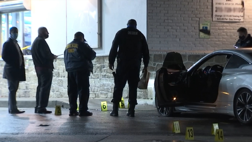 Detectives look at the ground as evidence markers lay on the ground surrounding a vehicle following a fatal carjacking in North Philadelphia.