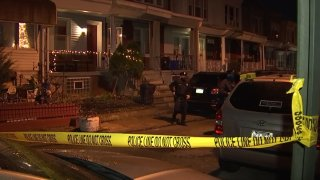 Crime scene tape surrounds a group of row homes in West Philadelphia as a police officer walks by following a fatal triple shooting.