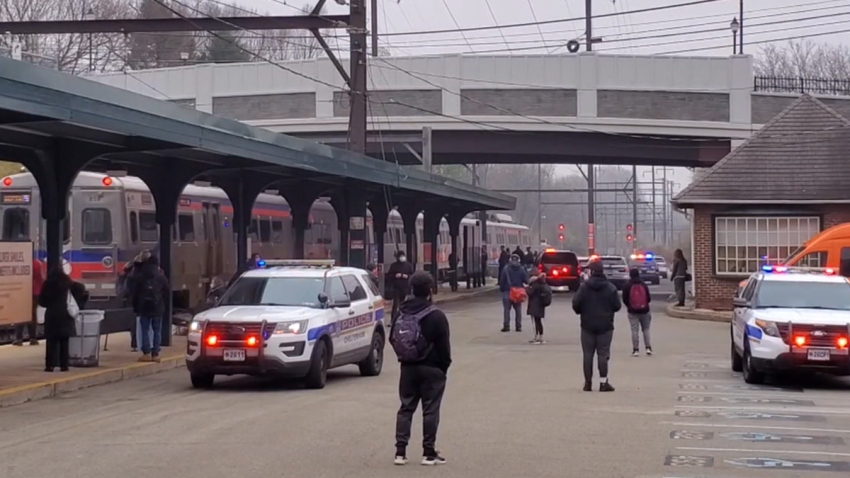 Passengers stand around as two police SUVs park near a SEPTA station where a train is halted following a crash that killed a man.