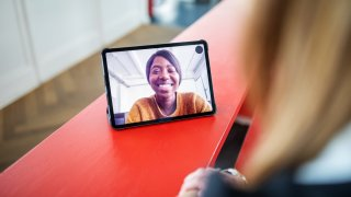 A woman is seen smiling through a tablet screen.