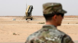 A member of the U.S. Air Force stands near a Patriot missile battery at the Prince Sultan air base in al-Kharj