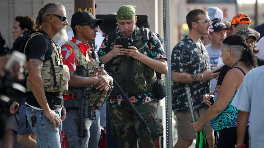 gun-carrying men wearing Hawaiian print shirts associated with the boogaloo movement watch a demonstration near where President Trump had a campaign rally in Tulsa, Okla