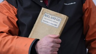 Bennett Konesni holds a book of sea shanties Thursday, Jan. 28, 2021, in Belfast, Maine. Work songs have helped sailors on long ocean journeys to break up the tedium. The genre is seeing a global revival among people bored and isolated by the coronavirus pandemic.