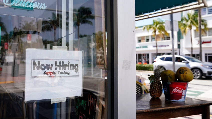 """A """"Now Hiring,"""" sign is shown in the window of a restaurant, Thursday, Jan. 7, 2021, in Miami Beach, Florida. America's employers likely cut back on hiring last month, and may have even shed jobs, as the economy suffers from a resurgent virus that has caused many consumers to cut back on spending and states and cities to reimpose business restrictions."""