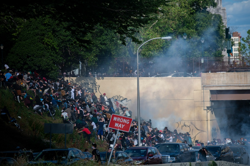 Protesters race up a hill after being shot by tear gas after a march through Center City on June 1, 2020 in Philadelphia, Pennsylvania.