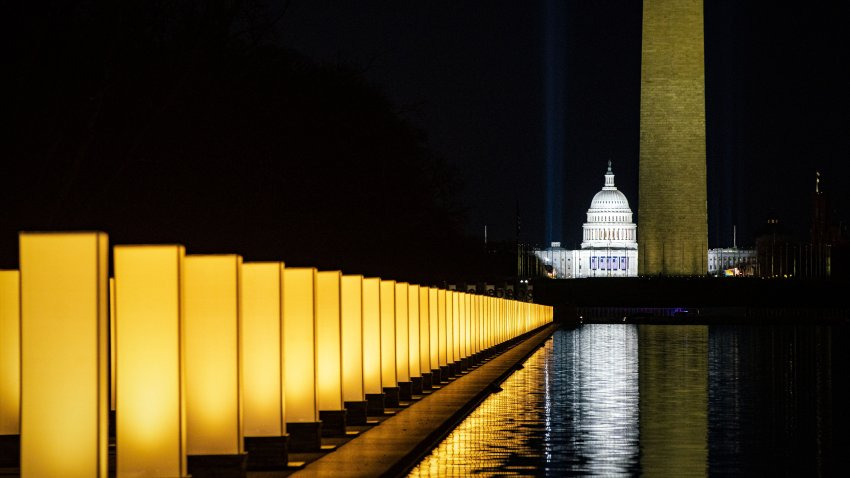 The U.S. Capitol, center, and Washington Monument, right, as lights surround the Lincoln Memorial Reflecting Pool during a Covid-19 memorial to lives lost on the National Mall in Washington, D.C., U.S., on Tuesday, Jan. 19, 2021. President-elect Joe Biden arrived in Washington on the eve of his inauguration with the usual backdrop of celebrations and political comity replaced by a military lockdown.