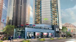 A rendering shows people walking down a sidewalk next to a brewery that sits in front of the former Embassy Suites Hotel, which is being converted into apartments in Philadelphia's Benjamin Franklin Parkway.