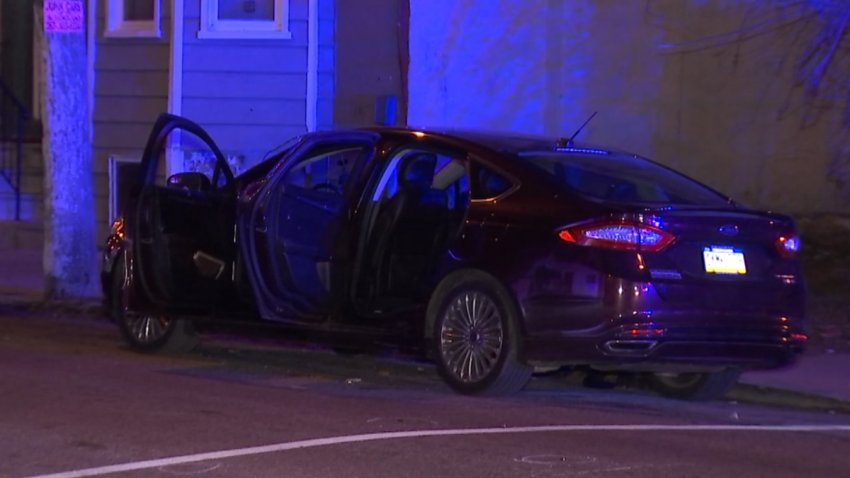 A dark-colored sedan is parked with its doors open near a sidewalk in the Mantua neighborhood of Philadelphia. Police say two women and a man were shot as they sat in the car.