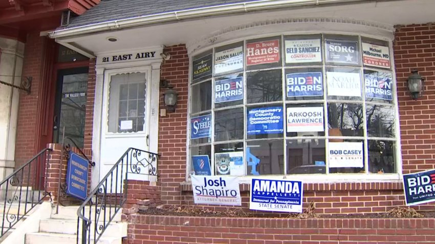 Multiple campaign signs and posters, including some supporting President Joe Biden and Vice President Kamala Harris, adorn the front window of the Montgomery County Democratic Committee's Norristown office.